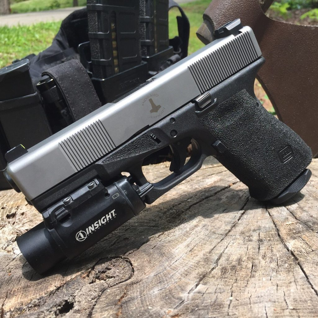 Glock 19 with stainless slide, angle cut serrations front and rear.